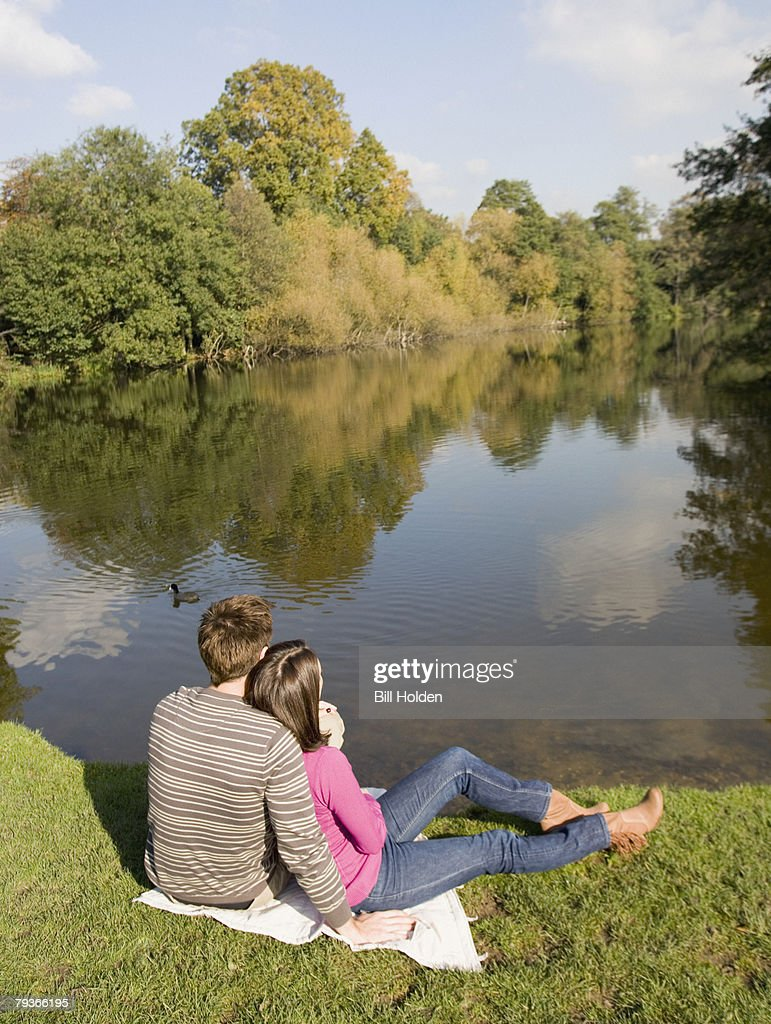 Couple outdoors sitting by a lake : Stock Photo