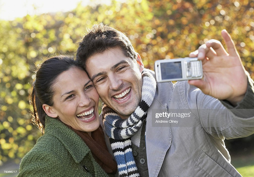 Couple outdoors taking a picture of themselves with camera phone : Stock Photo