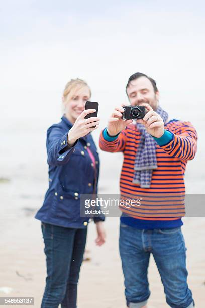 Couple outdoors, taking photographs using camera and smartphone