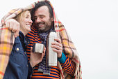 Couple outdoors, under blanket, drinking hot drink from drinks flask