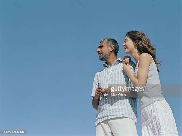 Couple outdoors, woman leaning on man's shoulder, low angle view