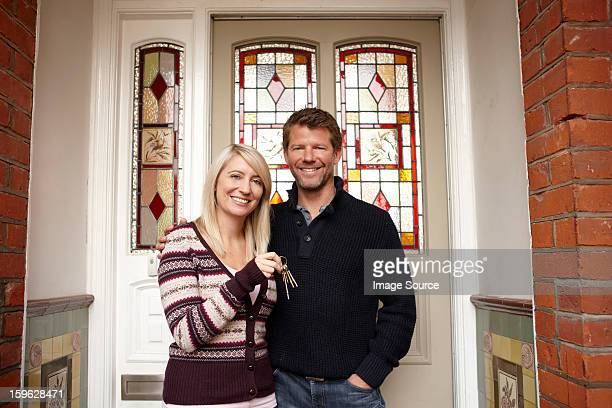 Couple outside new house with house keys