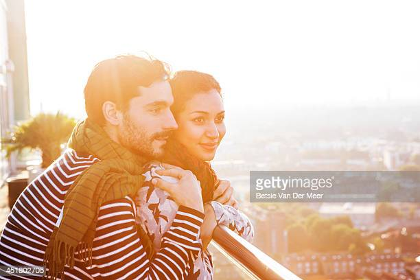 Couple overlooking the city at sunset.