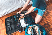 Happy young woman helping man in packing suitcase. Smiling couple are preparing for vacation. They are at home.
