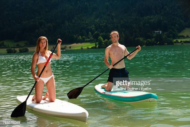 Couple Paddleboarding On Lake