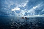 A couple paddles a sea kayak across a calm ocean beneath a storm.