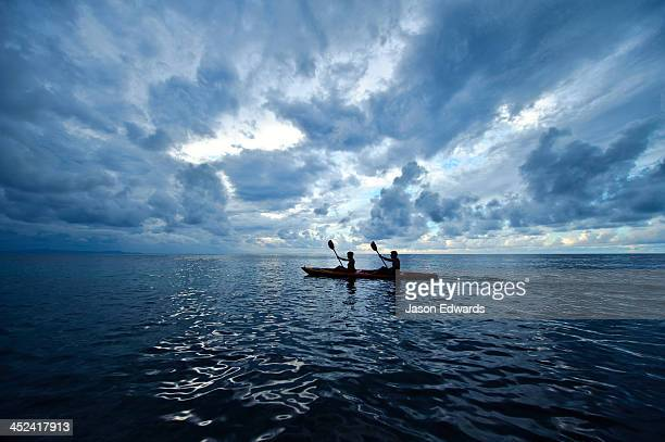 A couple paddles a sea kayak across a calm ocean beneath a storm.