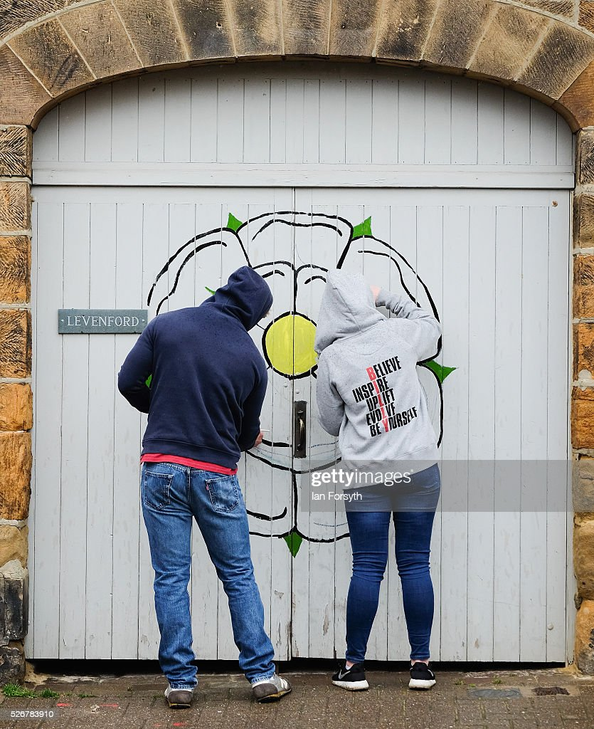 A couple paint a white Yorkshire rose on their garage door as they wait for stage three of the Tour de Yorkshire cycle race to pass on May 1, 2016 in Great Ayton, England. Returning for a second year the hugely popular race has grown to be one of the most spectacular events in the British sporting calendar. Up to a million people have lined the route along the three stages of the race which ends today with the 198km Middlesbrough to Scarborough leg.