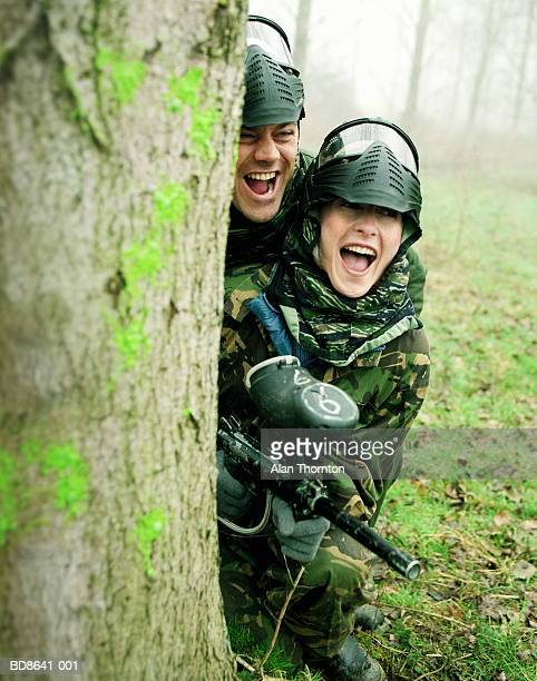 Couple paintballing, hiding behind tree
