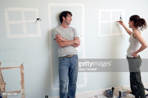 Couple painting doors and windows on an old wall : Stock Photo