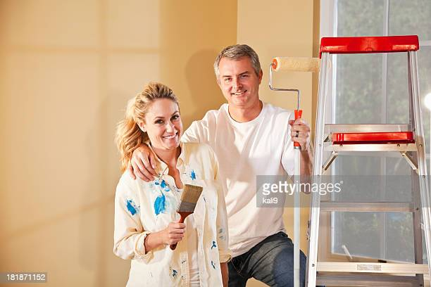 Couple painting home interior