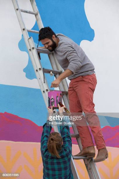 Couple painting mural wall outdoors