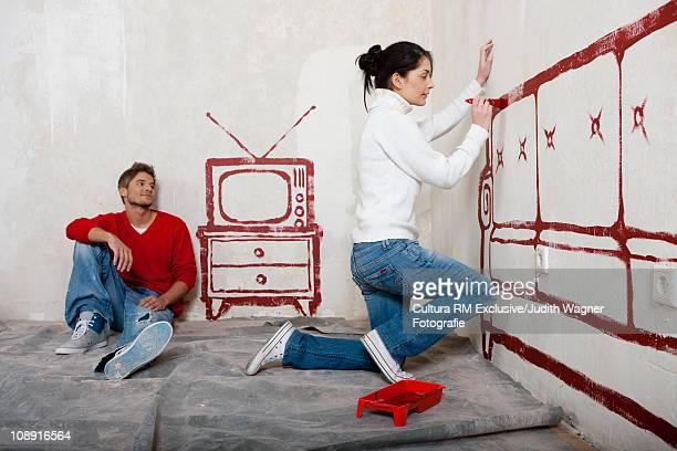 Couple painting sofa on wall