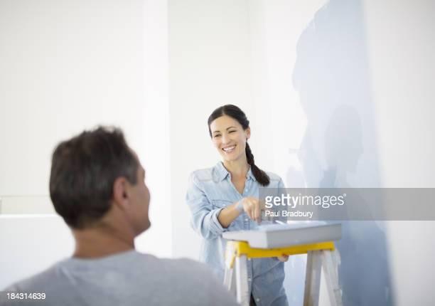 Casal Pintando a parede azul