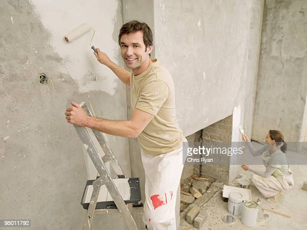 Couple painting wall in living room
