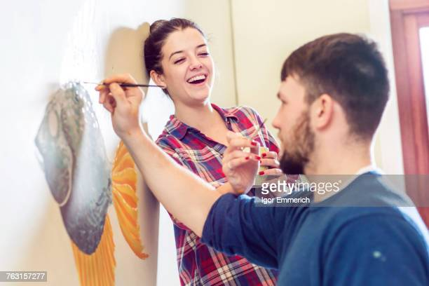 Couple painting wall mural smiling