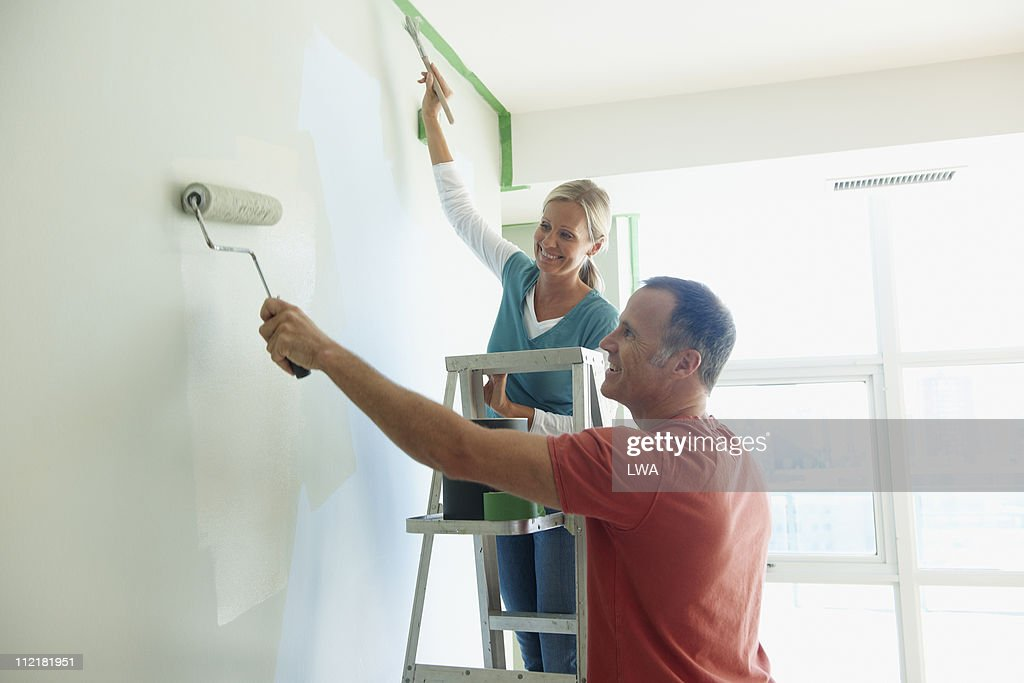Couple Painting Wall Together : Stock Photo