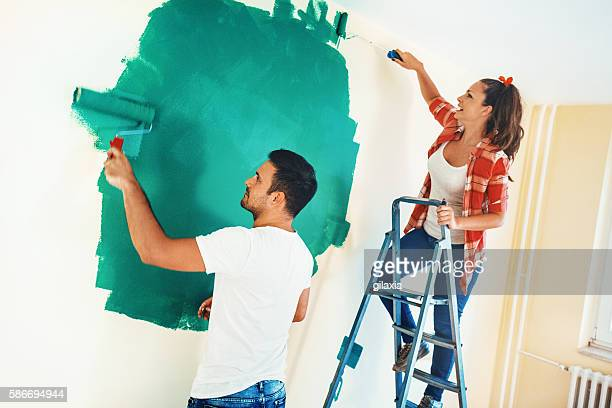 Couple painting walls.