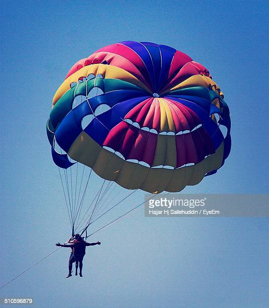 Couple parasailing in sky