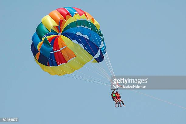 Couple parasailing, low angle view