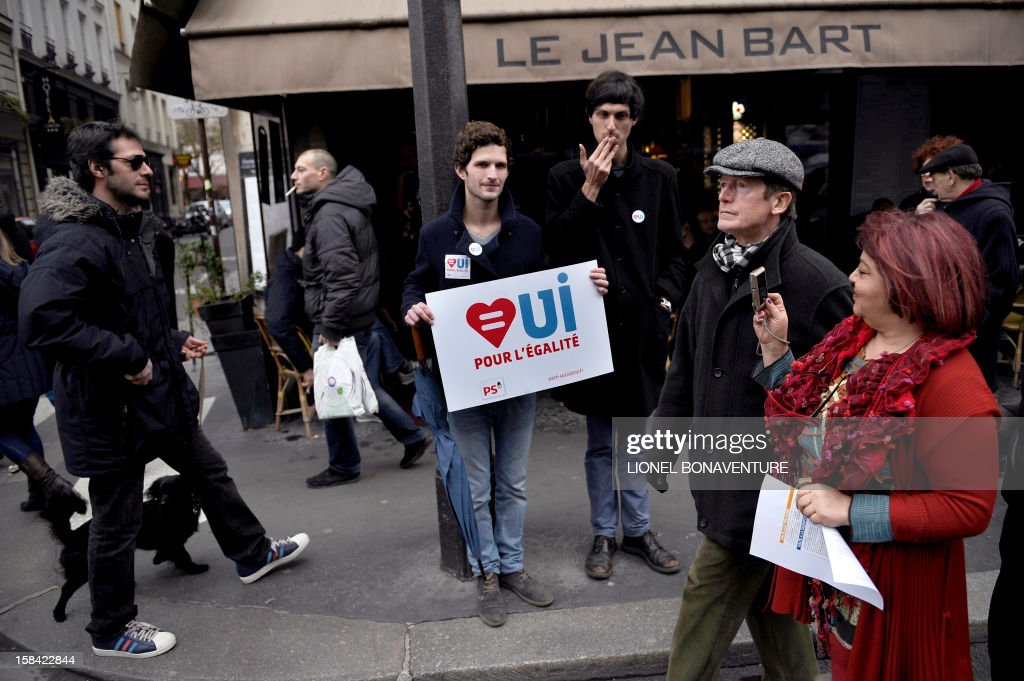 A couple passes by men taking part in a demonstration for the legalisation of gay marriage and LGBT (lesbian, gay, bisexual, and transgender) parenting, in Paris on December 16, 2012 .