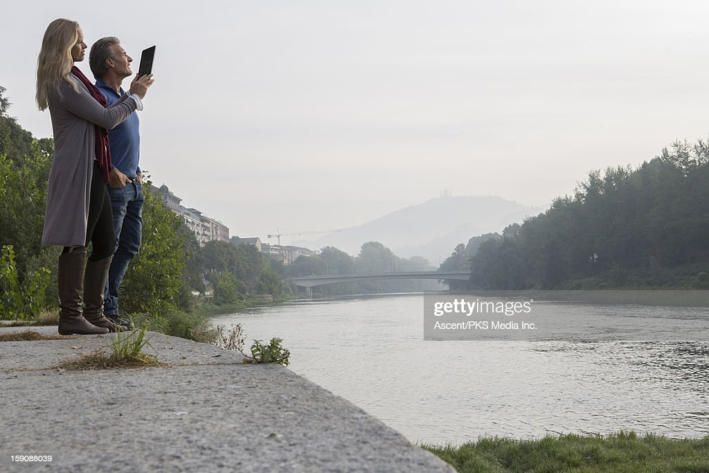 Couple pause at river's edge, take pic with tablet : Stock Photo