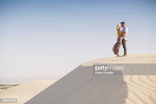 Couple pause in desert landscape, exchange kiss