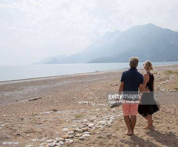 Couple pause on beach, look off towards sea, mtns