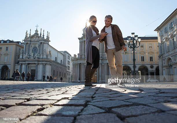 Couple pause to look at text message, piazza