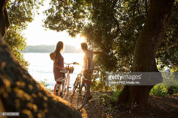 Couple pause with bikes, in forest above sea