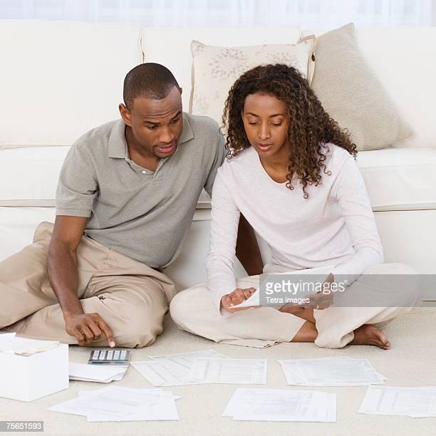 Couple paying bills on floor