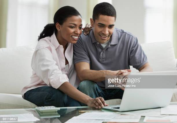 Couple paying bills online in living room