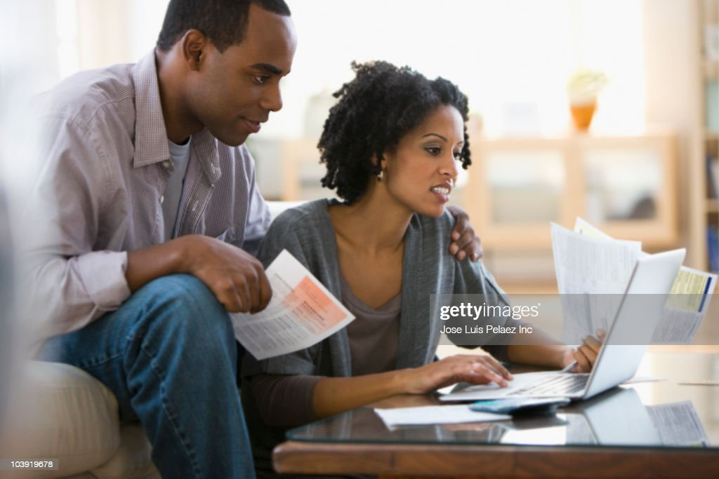 Couple paying bills using laptop