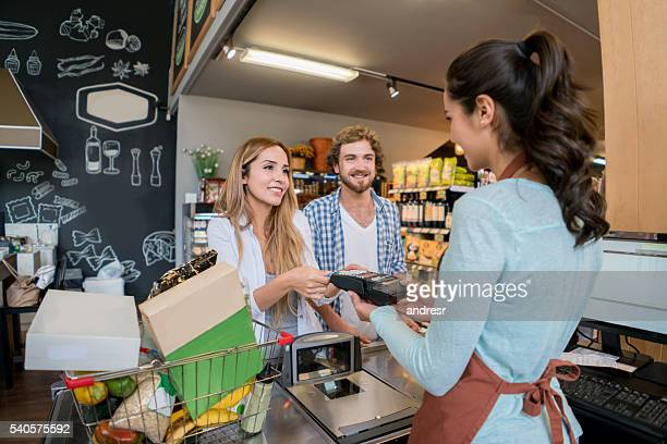 Couple paying by card at the supermarket