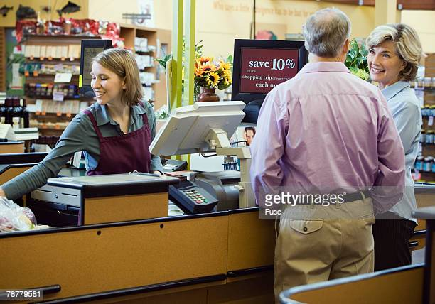 Couple Paying for Items at Supermarket Checkout