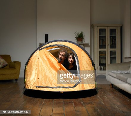 Couple peering from tent in living room : Stock Photo