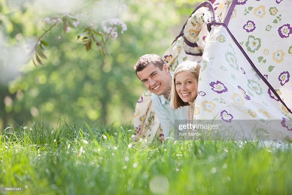 Couple peering out of tent at campsite : Stock Photo