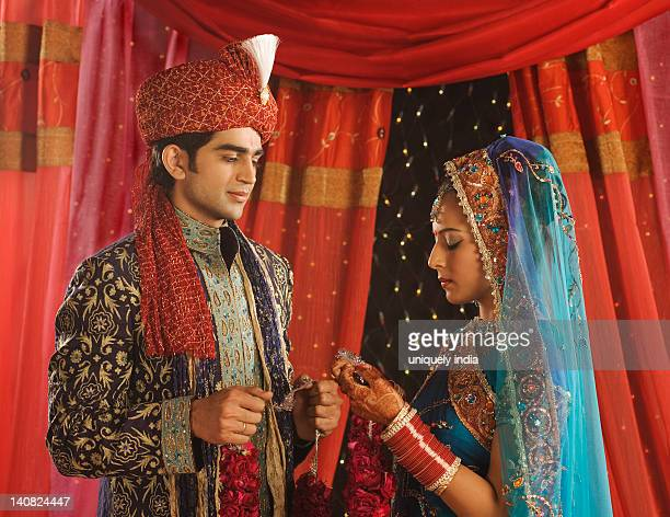 Couple performing Mala Badal ceremony in wedding mandap
