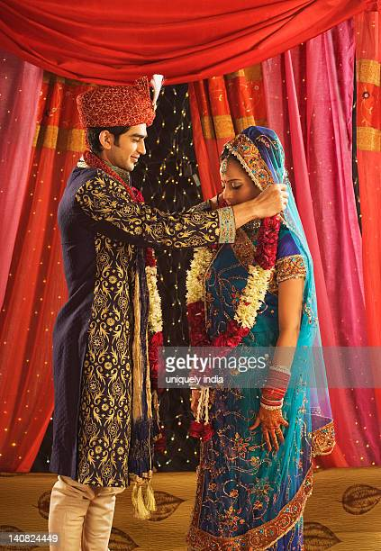 Couple performing Mala Badal ceremony in wedding mandap