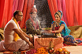 Couple performing religious ceremony in wedding mandap