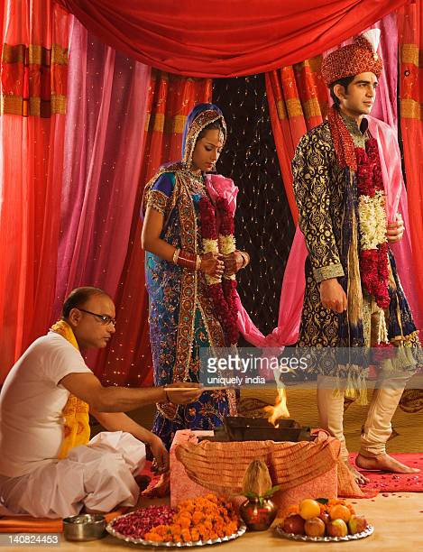 Couple performing Saptapadi ceremony in wedding mandap