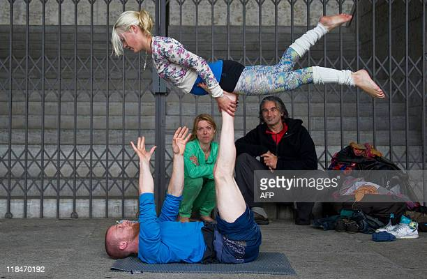 A couple performs 'acroyoga' during the World Culture Festival at Berlin's Olympiastadion July 2 2011 Thousands of people showed up for the festival...