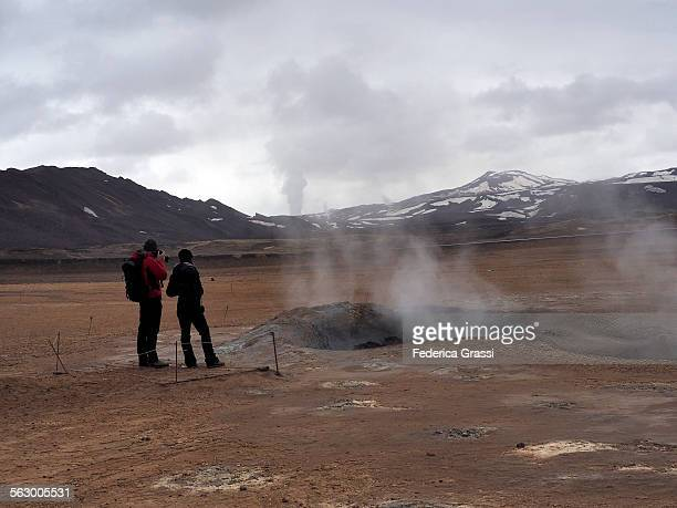 A Couple Photographing a Geiser in Iceland