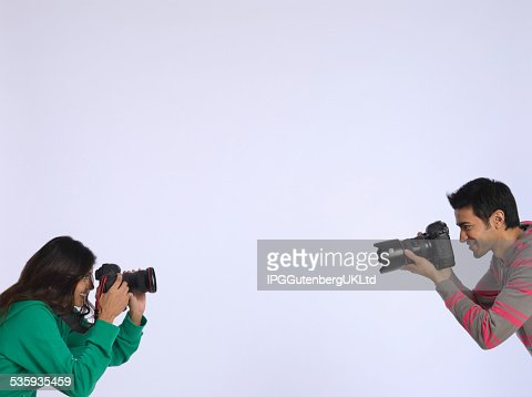 Couple Photographing Each Other In Studio : Stock Photo