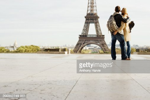 Couple photographing Eiffel Tower, rear view, ground view : Stock Photo