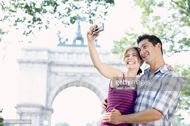Couple photographing self in front of monument