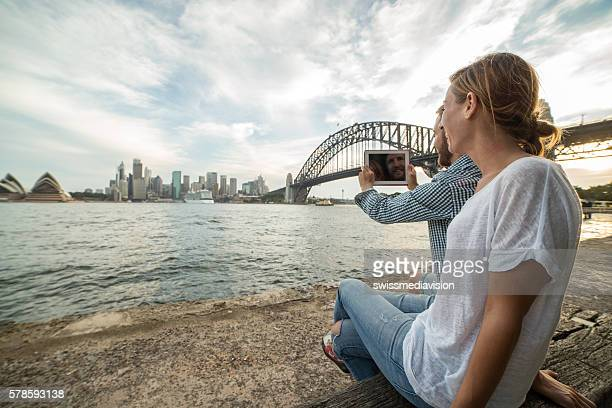 Couple photographing Sydney skyline using digital tablet