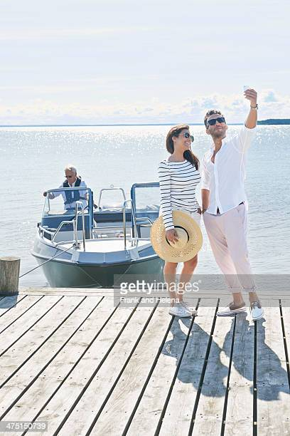 Couple photographing themselves on pier, Gavle, Sweden