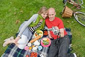 Couple picnicking in park with digital camera
