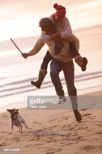 Couple piggyback on beach in winter with dog : Stock Photo